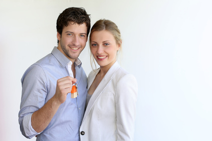 Young smiling couple holding keys of their new house